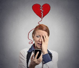 Sad woman with broken heart looking at her mobile phone isolated on grey wall background